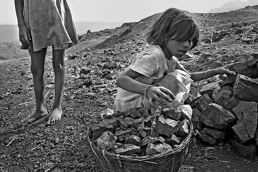 Children from the Jharia district collecting coking coal to be sold in the streets of Dhanbad, india.<br /> Here, due to the improper closure of abandoned mines and careless extraction techniques, the coal has been burning underground for a century. As soon as it turns to ashes, the ground collapses and the people are forced to move in shelters after the land has engulfed what remains of their burnt houses.<br /> Hand to mouth, they keep living in this wasteland, mostly surviving on the illegal sale of coal. In periods of more strict controls are the children, aged between four and eight years, to intercept the convoys leaving the mines to steal the coal that is then collected by other children and brought to the village.