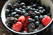 A bowl of summer berries including raspberries, blackberries and blueberries.