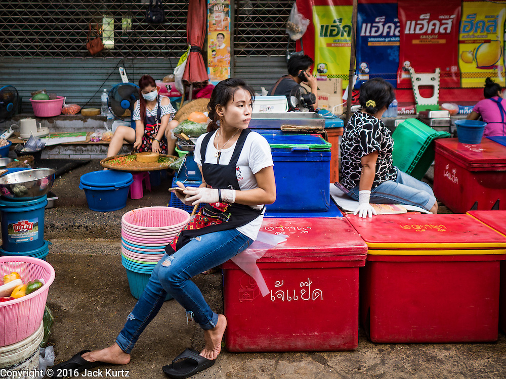 01 DECEMBER 2016 0 BANGKOK, THAILAND: A vendor in the traditional market on Lan Luang Road in Bangkok. The market is on the site of one of the first western style cinemas in Bangkok. The movie theatre closed years ago and is still empty but the market fills the streets around the theatre.     PHOTO BY JACK KURTZ