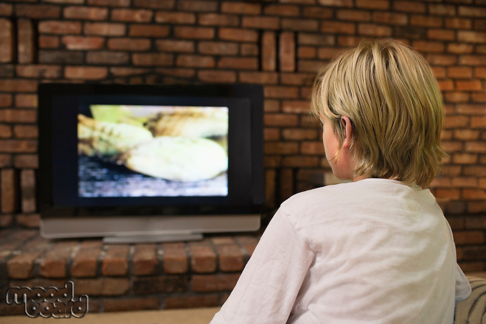 Boy (10-12) watching television back view