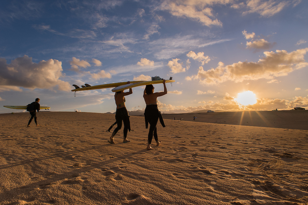 Two girls walking in the dunes at sunset while carrying a surfboard, Fuerteventura, Spain.