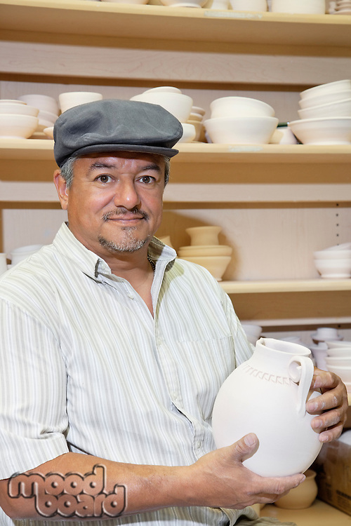 Portrait of a mature potter holding ceramic vase in workshop