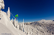 Eleven year old Parkin Costain jumps from cliff on a sunny day at Whitefish Mountain Resort in Montana model released