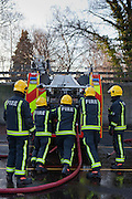 London Fire Brigade, station training session. Fire fighters put  the ladders back on the fire engine at the end.