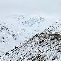 Road leading up to the summit of the Furka Pass (2431m) connecting Uri and Valais in the Swiss alps.  Photographed shortly before the road closed for a seven month winter. Historically this area, around Uri belonged to the National Redoubt, the final Swiss line of defence in the high alps, and is checked with the remains of millitray installations, many of them underground, still camouflaged.