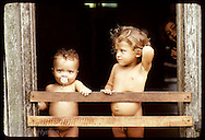 Boards across doorway of shack in Eirunepe slum keep these kids from falling down front steps. Brazil