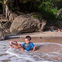 A young Costa Rican boy plays in the surf while his mother watches at los Suecos. Playa los Suecos is also called Mal Pais' hidden beach and it is known for its isolation, beauty, and snorkeling opportunities. It is located down a rough one-lane road past the fisherman's village and down a path by the border of Cabo Blanco National Park in Mal Pais, Costa Rica.