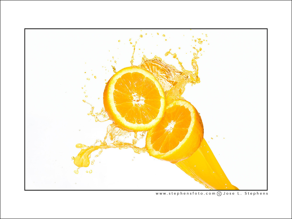 Splash liquids photography of orange juice splashing on half oranges against a white background