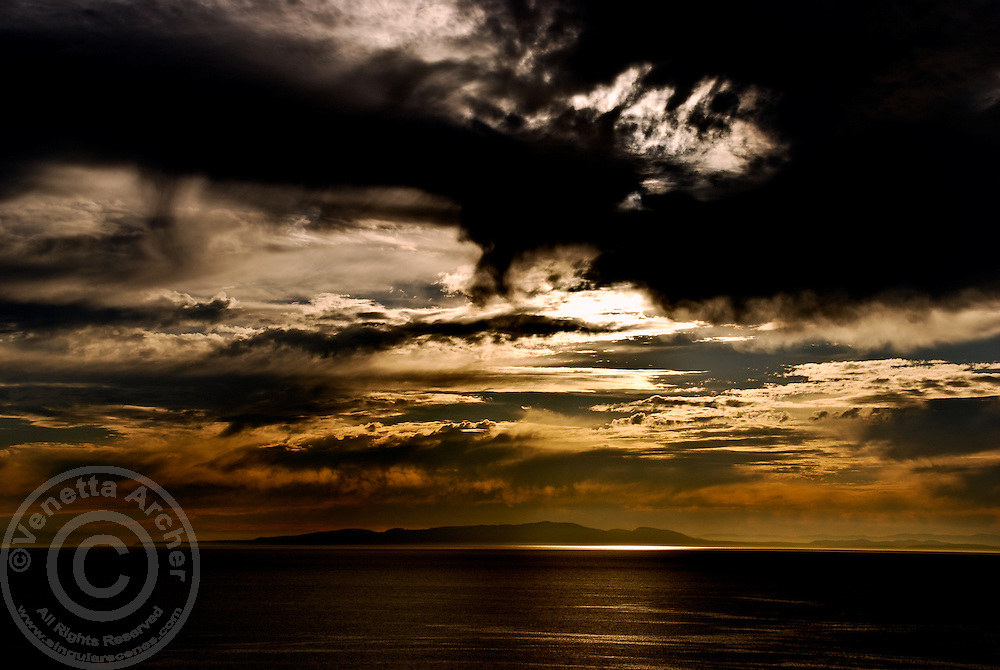 The clouds begin to part following a dramatic storm just as the sun is setting over White Rock Beach.