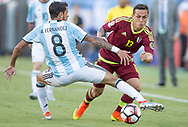 Offensive midfielder Luis Manuel Seijas of Venezuela passes by Argentinian defender Augusto Fernandez during the first half of a quarter-final matchup of the Copa America Centenario 2016 in Foxborough, Massachusetts, Saturday June 18, 2016.