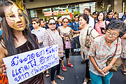 "09 JUNE 2013 - BANGKOK, THAILAND:   A White Mask protester dressed as Thai Prime Minister Yingluck Shinawatra walks through the crowd at Central World in Bangkok Sunday. The White Mask protesters wear the Guy Fawkes mask popularized by the movie ""V for Vendetta"" and the protest groups Anonymous and Occupy. Several hundred members of the White Mask movement gathered on the plaza in front of Central World, a large shopping complex at the Ratchaprasong Intersection in Bangkok, to protest against the government of Thai Prime Minister Yingluck Shinawatra. They say that her government is corrupt and is a ""puppet"" of ousted (and exiled) former PM Thaksin Shinawatra. Thaksin is Yingluck's brother. She was elected in 2011 when her brother endorsed her.    PHOTO BY JACK KURTZ"