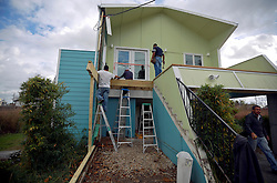 03 December 2013. Lower 9th Ward, New Orleans, Louisiana. <br /> Contractors replace the rotten stairs and front deck of a recently built Brad Pitt 'Make it Right' home on Tennessee Street. <br /> Photo; Charlie Varley