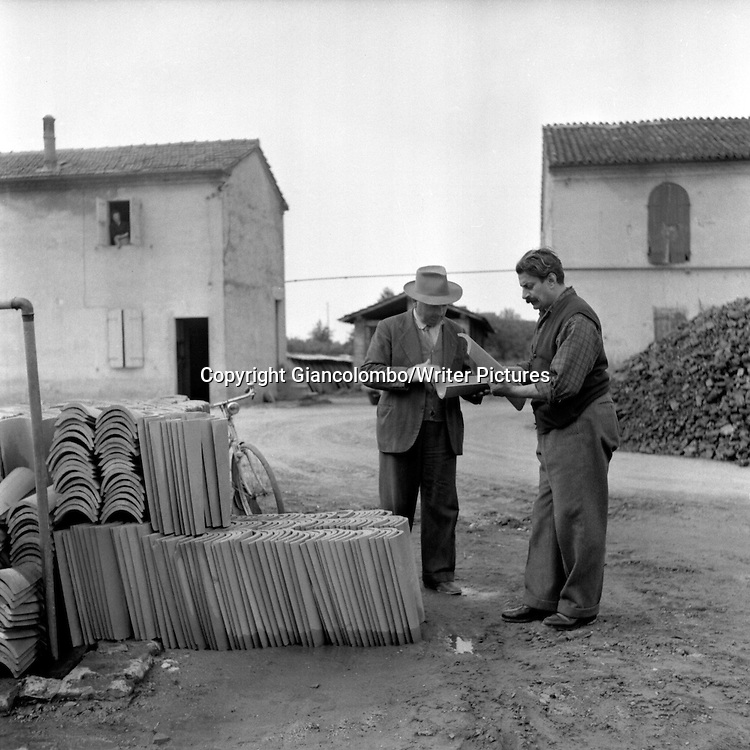 Giovannino Guareschi buying tiles at a furnace in Parma.<br /> 1954<br /> <br /> Photograph by Giancolombo/Writer Pictures<br /> <br /> WORLD RIGHTS, NO AGENCY, NO ITALY