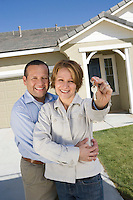 Portrait of mid-adult couple with keys to new house