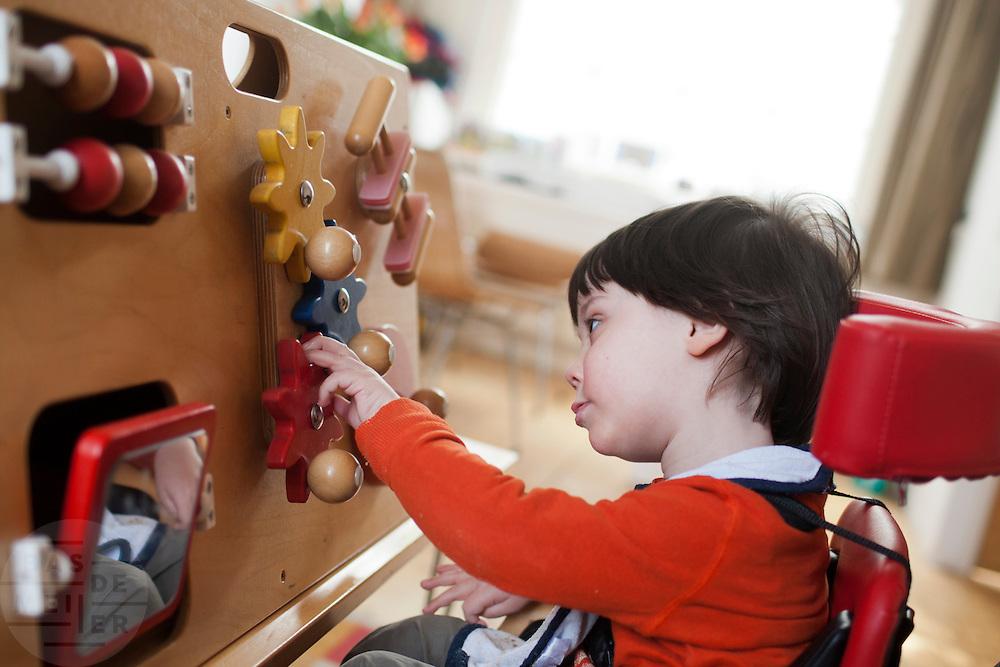 Hij speelt met een speciaal bord om zijn ontwikkeling te stimuleren.<br /> <br /> Playing with an activity center to stimulate his development.