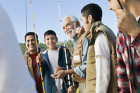 Male members of three generation family holding fishing rods outdoors smiling