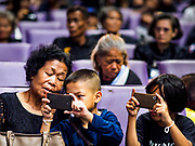 26 OCTOBER 2017 - BANGKOK, THAILAND:  Children take pictures of the televised broadcast of the royal funeral in the waiting area of Hua Lamphong train station during the funeral ceremony for Bhumibol Adulyadej, the Late King of Thailand. The king died on 13 October 2016 and was cremated 26 October 2017, after a mourning period of just over one year. The revered monarch was the longest reigning king in Thai history and is credited with guiding Thailand through the turbulent latter half of the 20th century.   PHOTO BY JACK KURTZ