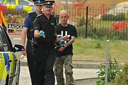 © licensed to London News Pictures. Norwich, UK  07/05/2011.A man is led away by police after a two day armed siege in Costessey has ended peacefully. One man has reportedly been arrested for firearms offences and two people arrested for wasting police time after a stand-off which lasted the best part of two days on the Hampdens development near Longwater Lane.  Please see special instructions for usage rates. Photo credit should read Alan Bennett/LNP