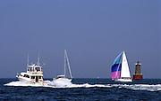 motoryacht speeding past sailboats; wake; miniature lighthouse buoy; recreation; Chesapeake Bay; Maryland