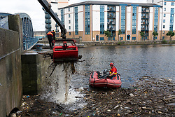 Clean up of debris collected at bridge on Water of Leith river at Leith after heavy rainfall, Scotland, UK