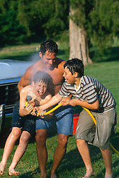Two boys and a man playing with a garden hose outdoors during Summer