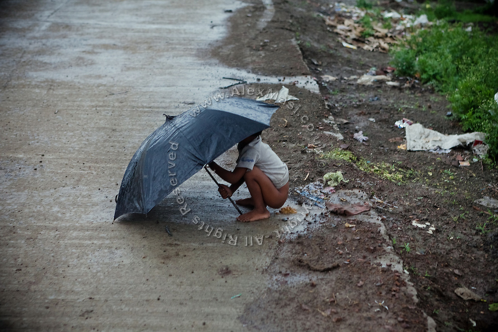 A young boy is defecating on the streets of the impoverished Oriya Basti Colony in Bhopal, Madhya Pradesh, India, near the abandoned Union Carbide (now DOW Chemical) industrial complex.