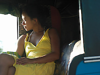 Young woman sitting in shade looking away