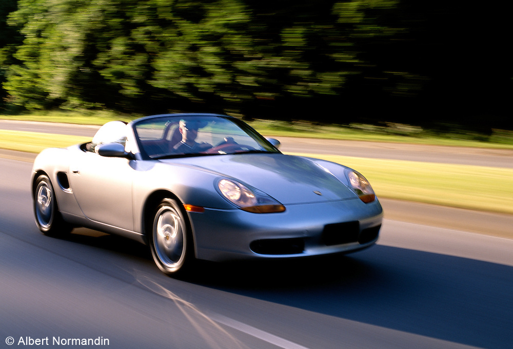 Silver Porsche on road at speed