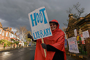 Wendy Sullivan, an artist, pensioner and lifelong activist stands outside Carnegie Library in Herne Hill, south London asking passing motorists to hoot their support, while occupiers remain inside the premises on day 8 of its occupation, 7th April 2016. The angry local community in the south London borough have occupied their important resource for learning and social hub for the weekend. After a long campaign by locals, Lambeth have gone ahead and closed the library's doors for the last time because they say, cuts to their budget mean millions must be saved.