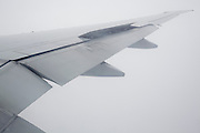 wing of passenger airplane in cloud fog during early stage of landing