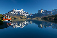 Hones of Paine and Paine Grande reflect in the calm waters of Lago Pehoe, Torres del Paine National Park, Chile