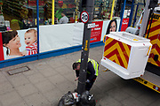A workman attaches ties to a lamp post on the Walworth Road in the south London borough of Southwark, on 7th March 2019, in London, England.