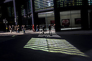A cyclist pedals through reflected light shining from a City of London office building.