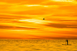 ©Licensed to London News Pictures. 18/09/2019 Aberystwyth UK. <br /> The sun setting gloriously over  Cardigan Bay silhouettes a person paddle-boarding on the calm sea the end of a day of unbroken clear blue skies and warm September sunshine in Aberystwyth ,  as the 'indian summer' mini heat-wave continues over much of the souther parts of the UK. Photo credit Keith Morris/LNP