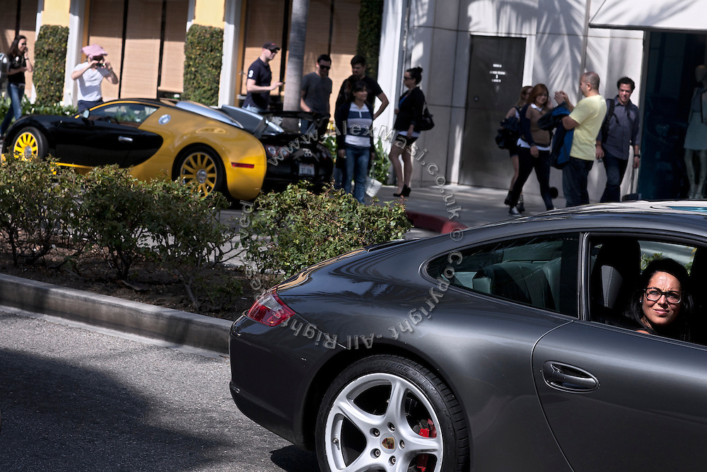 A woman sitting inside a Porsche car is looking outside the window on Rodeo Drive, the renowned shopping avenue running across Beverly Hills, Los Angeles, California, USA.