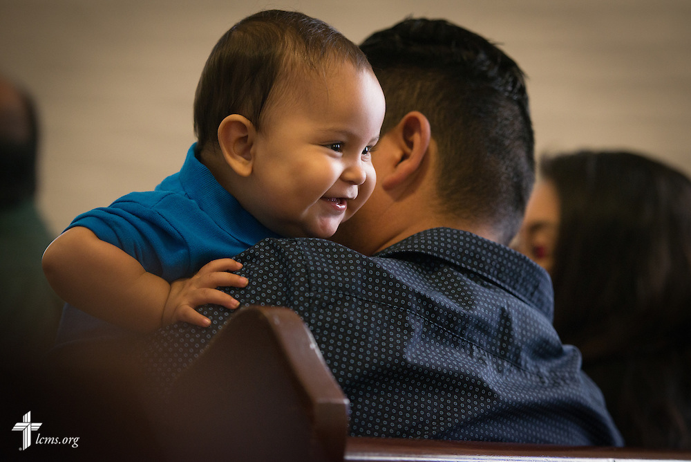 Daniel Anthony Lopez eyes a parishioner behind him as he plays on the lap of his father Daniel Lopez during worship at El Calvario Lutheran Church on Sunday, April 17, 2016, in Brownsville, Texas. LCMS Communications/Erik M. Lunsford