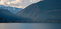 Ticino, Southern Switzerland. View of the town of Brissago and the mountains beyond from across Lake Maggiore.