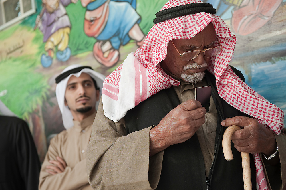 A Kuwaiti senior holding his nationality card as he prepares to vote at a polling station in Kuwait City in the February 2 parliamentary elections. A total of 400,296 Kuwaiti men and women are eligible to vote to choose from among some 285 candidates, including more than 20 women candidates, for a new 50-seat parliament.