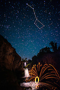 A celestial feast: sparks fly from a Catherine wheel below Celestial Falls and the Big Dipper (The Plough), White River Falls State Park, Wasco County, Oregon, USA.