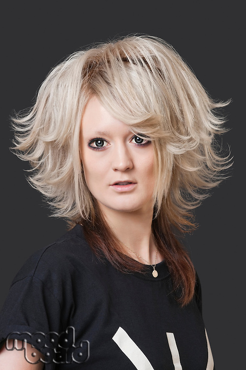 Portrait of young woman with modern hairstyle over black background