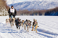 Musher Danny Beck competing in the Fur Rendezvous World Sled Dog Championships at Campbell Airstrip in Anchorage in Southcentral Alaska. Winter. Afternoon.