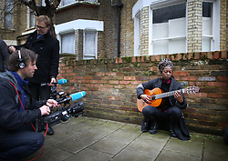 © Licensed to London News Pictures. 11/01/2016. London, UK. Ese Okorodudu plays the guitar and sings a tribute outside the Brixton house that David Bowie lived in. The Death of David Bowie, who was born in Brixton, has been announced today.  Photo credit: Peter Macdiarmid/LNP