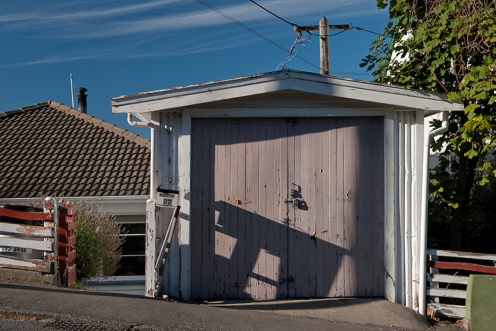 Morning sunlight casts shadow on a traditional wooden garage door, Lyttelton. New Zealand