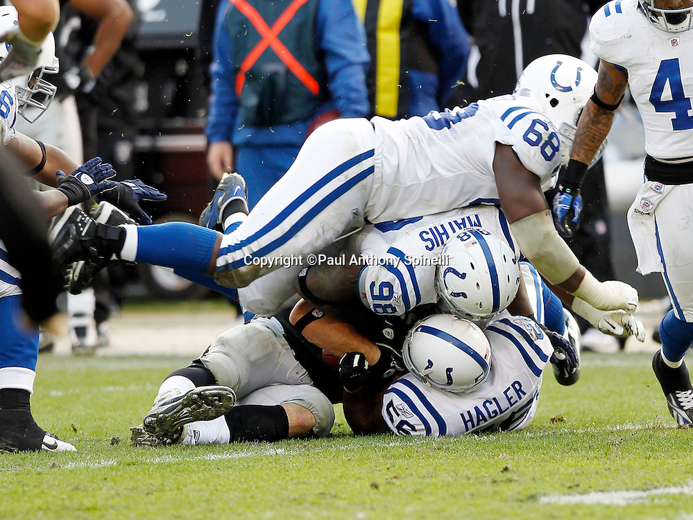 Indianapolis Colts defensive tackle Eric Foster (68) piles on top of a gang tackle with Indianapolis Colts defensive end Robert Mathis (98) and Indianapolis Colts linebacker Tyjuan Hagler (56) during the NFL week 16 football game against the Oakland Raiders on Sunday, December 26, 2010 in Oakland, California. The Colts won the game 31-26. (©Paul Anthony Spinelli)