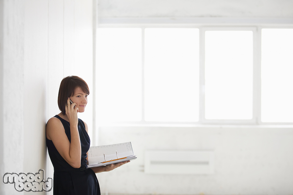 Business woman on holding file in empty warehouse