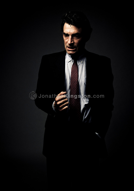 Front view of a mature man in a business suit, looking down, with his arm raised in contemplation, in Santa Barbara, California. Three quarter length studio shot against a dark background. (releasecode: jk_mr1025) (Model Released)