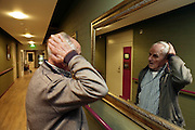 senior man looking at himself in the mirror and adjusting his hair