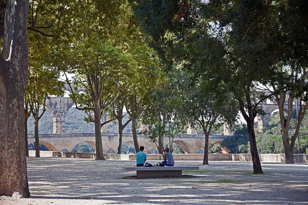 A couple rests in a tree-shaded park at the approach to the Pont du Garde.  Built by the Romans circa 19 B.C., this wonder of stone was a major link in a 30-mile canal that brought water to Nimes.  It is the world's second highest standing Roman structure.