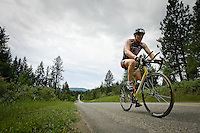 JEROME A. POLLOS/Press..Jim Huff, from Parlier, Calif., pedals his way up a steep grade during the 112-mile bike ride Sunday during the Ford Ironman Coeur d'Alene.
