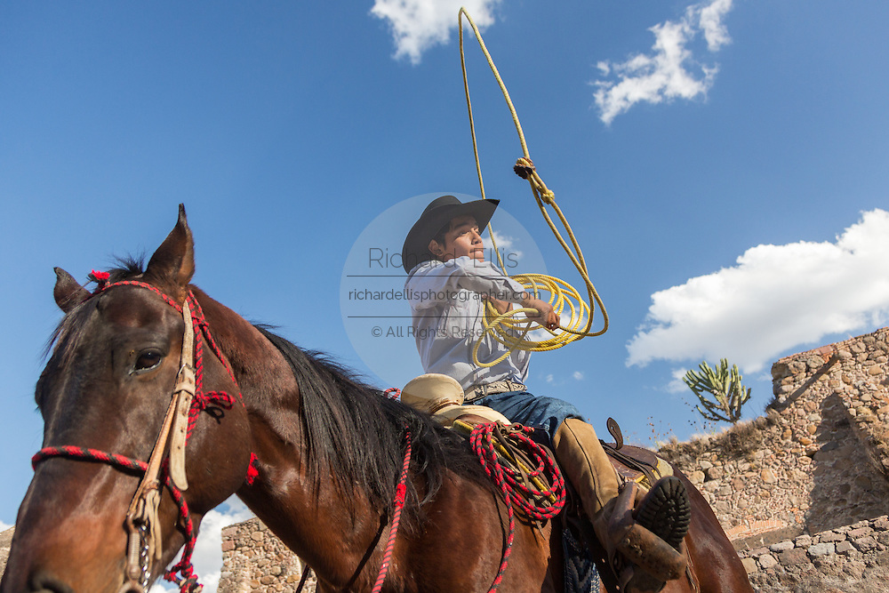 A Mexican charro or cowboy practices roping skills on his horse before a Charreada competition at a hacienda ranch in Alcocer, Mexico. The Charreada is a traditional Mexican form of rodeo and tests the skills of the cowboy at riding, roping and controlling cattle.